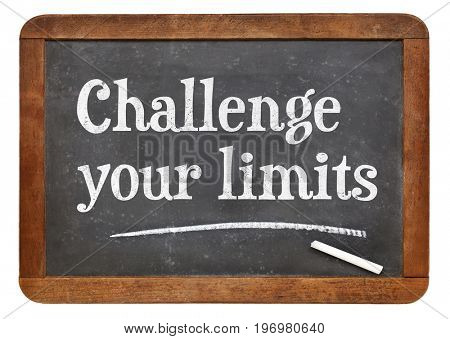 Challenge your limits - white chalk text on a vintage slate blackboard