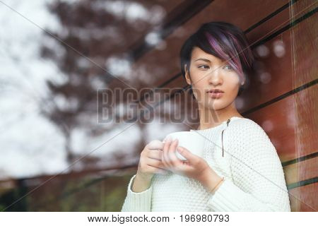 Shot through glass of young woman in sweater posing with cup of coffee in hands.