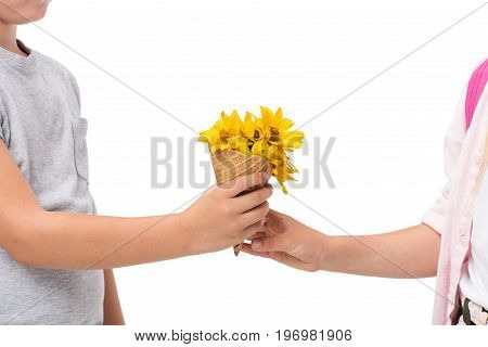 cropped shot of cute little children holding waffle cone with yellow flowers isolated on white