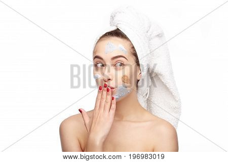Young woman with white towel on head and cosmetics on face posing surprisingly on white.