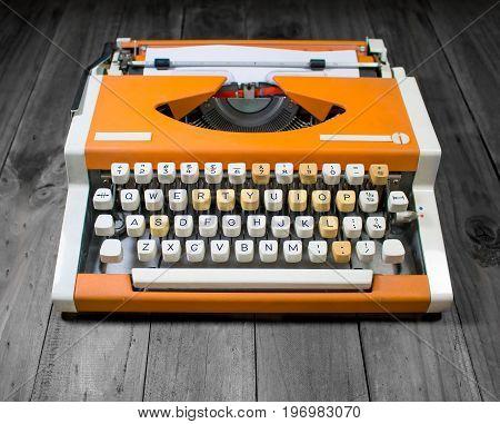 orange typewriter on the old wooden desk