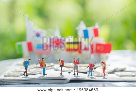 Tiny miniature model of travelers or backpackers are standing on a passport and a pile of coins with international flags background using as traveling journey travel to destination background concept.