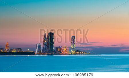Batumi, Adjara, Georgia - May 25, 2016: Panorama of illuminated resort town at sunset. Radisson Blu Hotel, Black Sea Technological University, Porta Batumi Tower, ferris wheel and Alphabet Tower