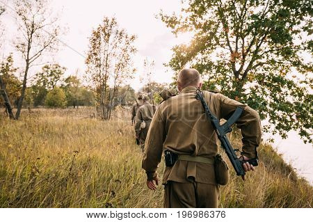 Group Of Reenactors Men Dressed As Russian Soviet Red Army Infantry Soldiers Of World War II Marching In Autumn Field With Weapons At Historical Reenactment.