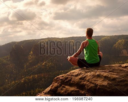 Man On Top Of Mountain In Yoga Pose. Exercise Yoga On Edge With A Breathtaking View