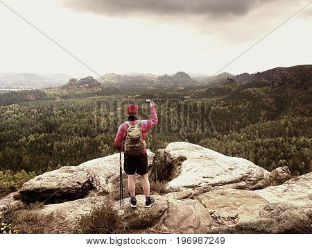 Mobile Phone Photographer. Tourist On The Rocky Edge Take Phone Pictures. Hiking In Mountains