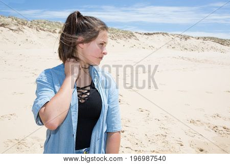 Girl On In Sand Beach Looks Thoughtfully Into Distance To Last Ray Of Sunset, Falling On Hectic Sea