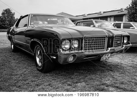 PAAREN IM GLIEN GERMANY - MAY 23 2015: Mid-size car Oldsmobile Cutlass Supreme 1972. Black and white. The oldtimer show in MAFZ.