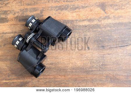 Old prism black color binoculars on vintage wooden background side view closeup