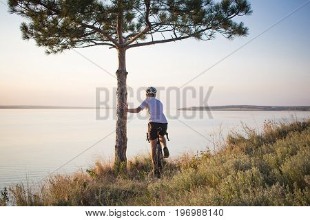 picture of bicycle rider standing on the hill near pine and looking on sunset in lake