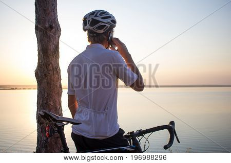 man in helmet standing and speaking phone with beautiful lake on backgraund