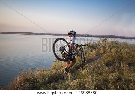 Young athlet walking up hill with bicycle in hands, beautiful lake background