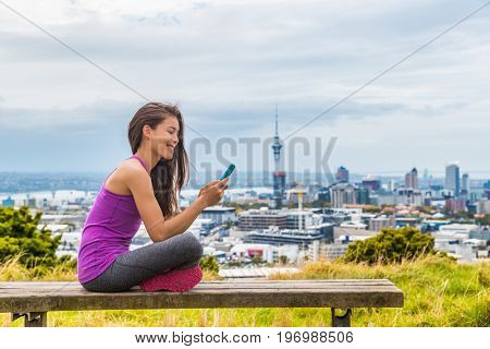 Auckland city runner girl using mobile phone app at skyline summer park. View of cityscape from Mount Eden, in North Island, New Zealand. Girl taking break outdoors after running.