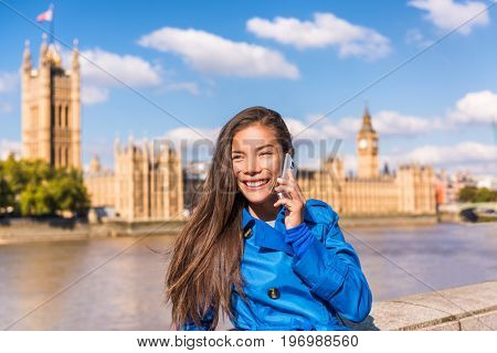 London city businesswoman calling on mobile phone app talking to cellphone at Westminster Houses of Parliament background. Asian tourist woman Europe travel destination, England, Great Britain.