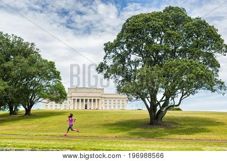Auckland city park running jogging girl on green grass and trees at Auckland Domain park with Memorial museum . Active lifestyle woman training. Famous travel tourist attraction in New Zealand.