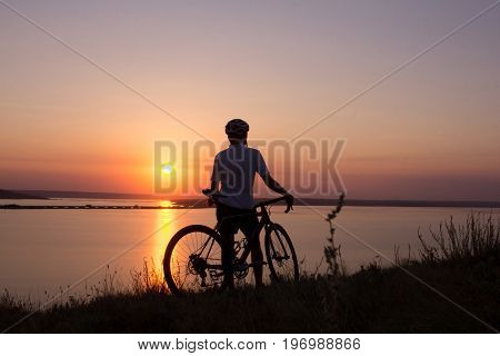 silhouette of a cyclist  watching sunset in lake, male bicycle rider in helmet during sunset