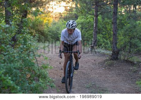 Young athlete riding on his professional mountain or cyclocross bike in the forest during sunrise