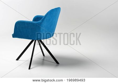 Studio Shot Of Stylish Chair With Blue Fabric Top And Triangular Metallic Legs On White