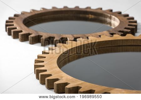 Close-up Cropped View Of Mirrors Framed By Wooden Cogwheels Lying On White