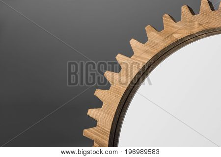 Close-up Cropped View Of Mirror Framed By Wooden Cogwheel On Gray