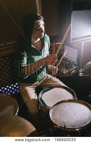 Drummer playing drums in recording studio. Rehearsal before live concert