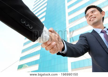 Handshake of businessmen with smiling face - greeting dealing merger & acquisition concepts