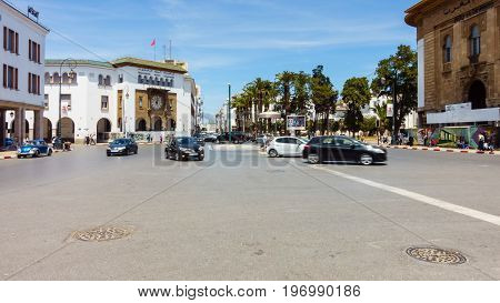 Rabat Morocco - May 06 2017: Cars are driving on the Central Square in Rabat Morocco past the French colonial telegraph and post office building while people are walking about. Motion blur.
