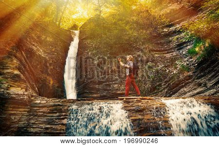 The tourist makes a self-portrait against the backdrop of a landmark waterfall