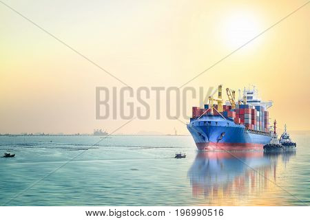 Logistics and transportation of International Container Cargo ship with tugboat in the ocean at sunset sky Freight Transportation Shipping