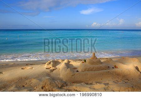Battered sandcastles on the sunny ocean background.