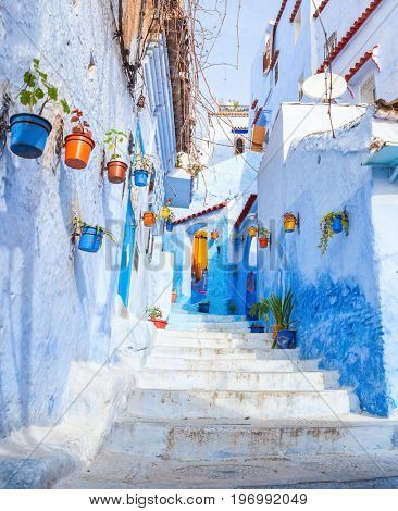 Colorful  narrow old street in medina at sunny morning , Chefchaouen, Morocco.