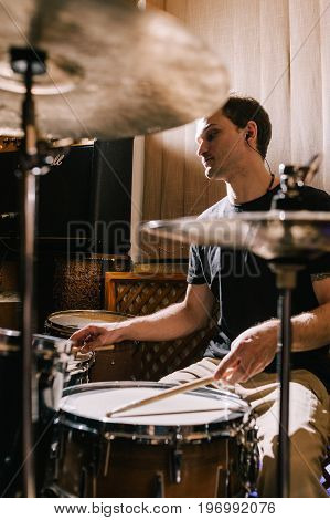 Man drummer playing drums in recording studio. Rehearsal before live music concert