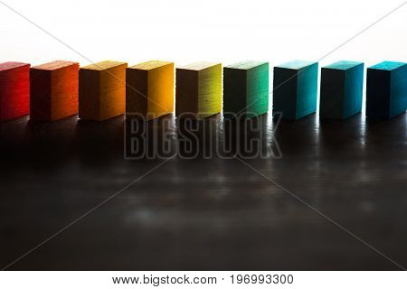 Colored wooden blocks diagonally aligned in light and shadow. On an wooden table. For something with concept of variations or diversity. Plenty of copy space for cover or header image usage.