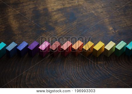 Colored wooden blocks diagonally aligned on old vintage wooden table. For something with concept of variations or diversity. Plenty of copy space for cover or header image usage. low key, shallow DOF.