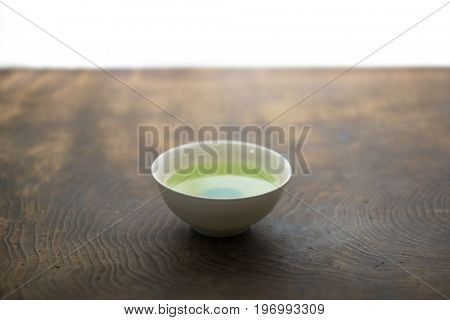 A cup of green tea in light and shadow on a old table.