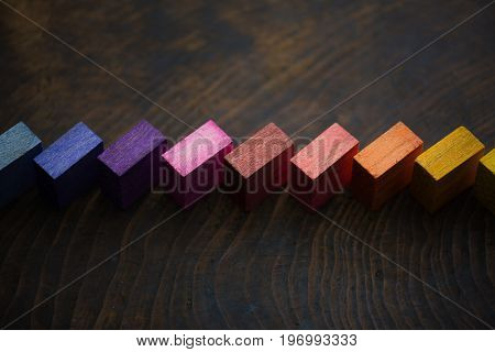Colored wooden blocks diagonally aligned on old vintage wooden table. For something with concept of variations or diversity. Intentionally shot with shallow depth of field, and low key.