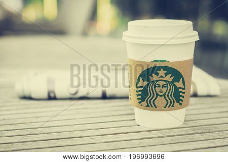 Bangkok Thailand - Feb 26 2015 : Starbucks take away coffee cup with newspaper on the table Starbucks brand is one of the most world famous coffeehouse chains from USA - vintage tone image