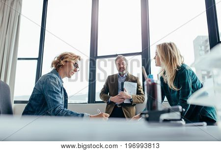 Business people working in modern office. Businesswoman sitting at her desk with colleagues standing by.