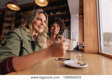 Two young woman sitting at cafe and having coffee. Female friends drinking coffee at restaurant.