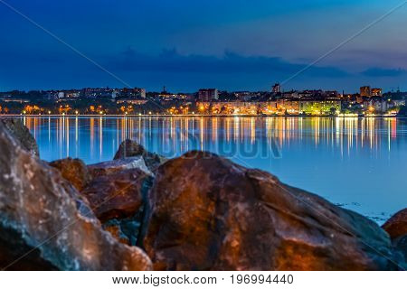 The lights of the Eastern European city are reflected in the lake. Stone blocks in the foreground.
