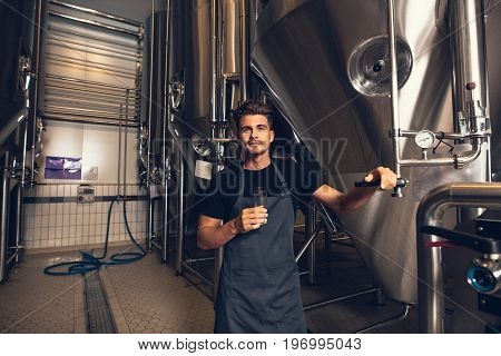 Male Brewer Standing By Tank In Brewery