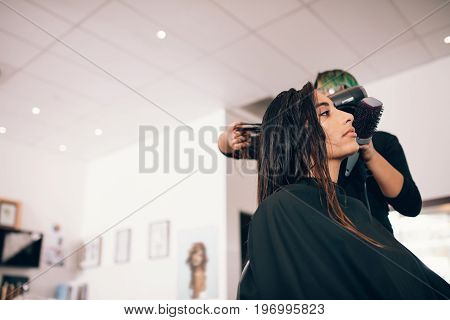 Female hair stylist using blower and brush to dry hair. Woman at a sophisticated beauty parlor getting a hairdo.