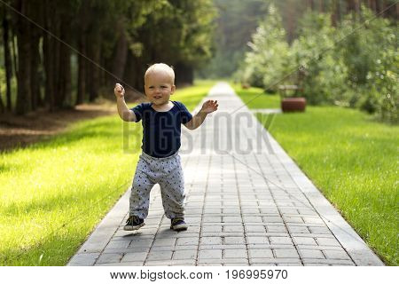 Baby's First Steps.the First Independent Steps. Cute Boy On The Walk