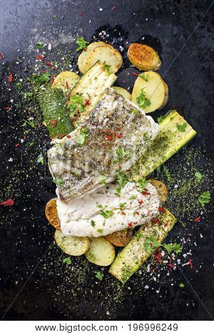 Fried cod fish fillet with vegetable and potatoes as top-view on old metal sheet