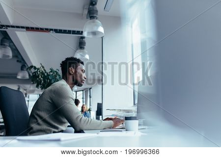 Side view of young african man working in office. Male executive sitting at his desk and working on desktop computer.