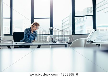 Female manager sitting at her desk and working on laptop. Beautiful young woman looking busy working on housing project plans.