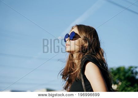 Young beautiful woman in sunglasses walking along a street in a city in the fresh air.