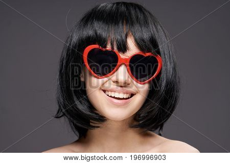 Young beautiful woman on a black background in sunglasses-hearts.