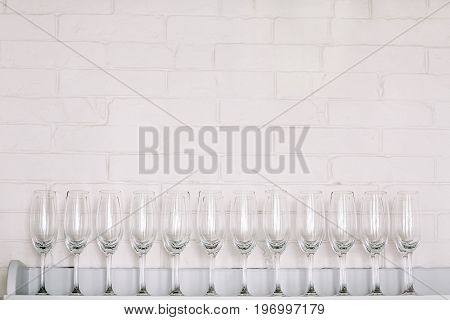 champagne glasses lined up in front of a white brick wall