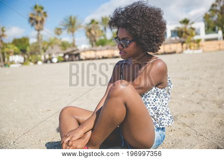 Beautiful Pensive Afro American Woman Sitting On Beach